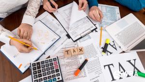 imagem pra simbolizar a discussão sobre impostos entre Brasil e Estados unidos - imagem cheia de documentos, calculadora e a palavra taxa em inglês