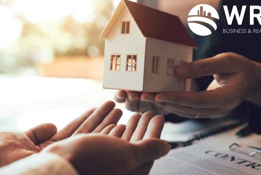 Um par de mãos entregando uma casa para outro par - simulando a compra do imóvel