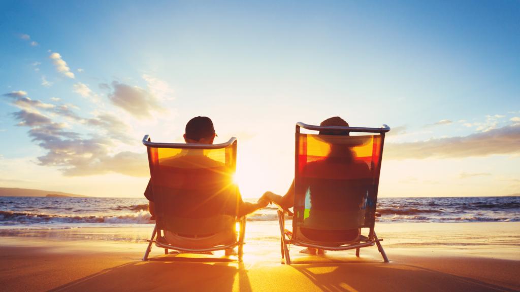 Imagem de dois idosos assistindo o pôr do sol na praia