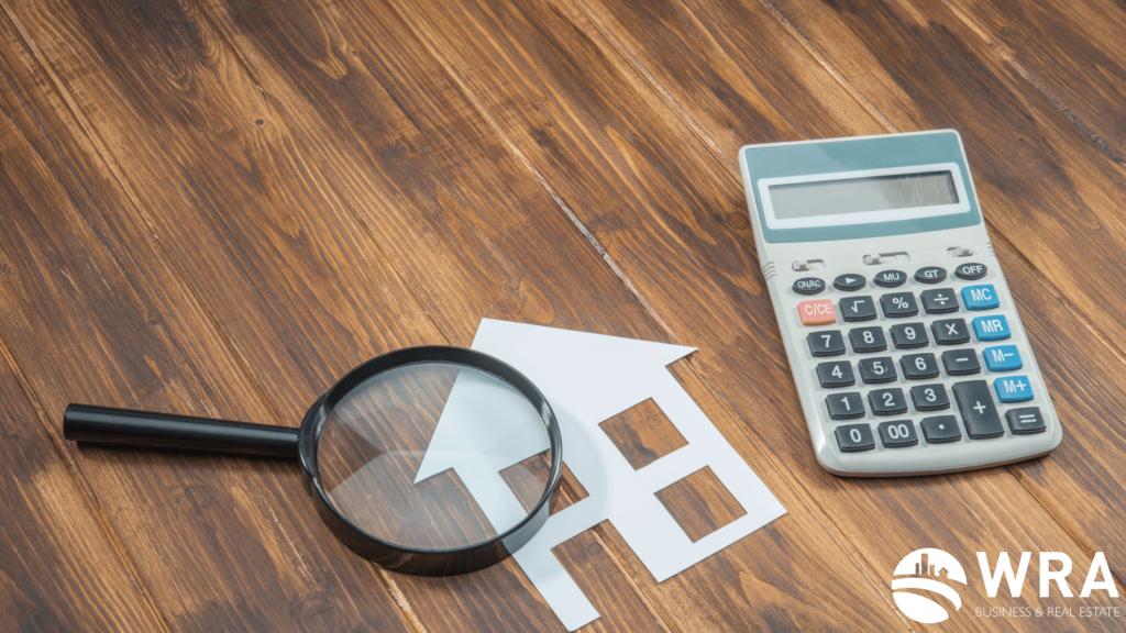 Imagem de uma calculadora, uma lupa e uma casa. Simbolizando a busca e os cálculos feitos para comprar um imóvel